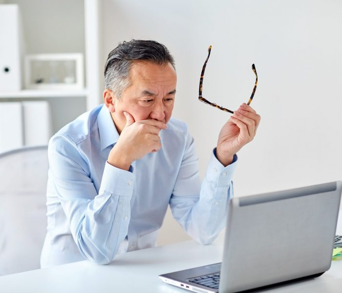 businessman-with-eyeglasses-and-laptop-at-office-PV2TDWD
